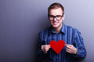 man in glasses holding a red heart