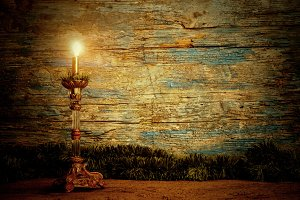 Old candle lit on a rustic wooden