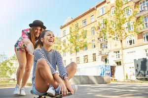 Fun loving young women playing on a skateboard