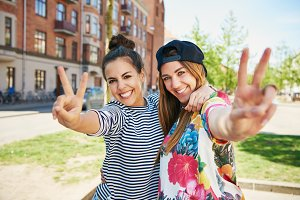 Two friends gesturing a V symbol with fingers