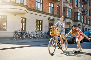 Cute girl on bike pulling friend on skateboard