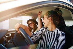 Two young women having fun driving along a street