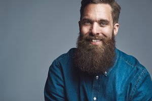 Close up on smiling male in denim shirt and beard