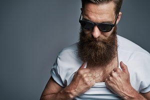 Bearded man in sunglasses showing chest hair