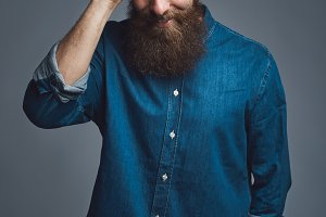 Cheerful man in beard combing his hair