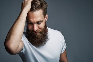 Thinking bearded man holding hair and laughing