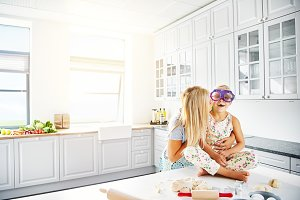 Mother kissing her daughter in kitchen