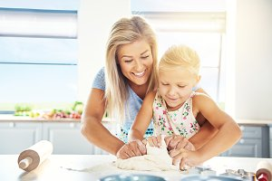 Adoring young mother teaching her daughter to bake
