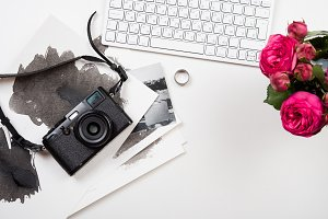 keyboard, pink flowers and photo camera on white table, photogra