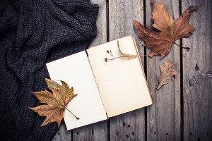 empty vintage book and knitted sweater with autumn leaves