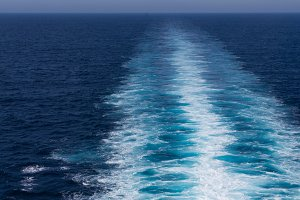 White wake trails behind a fast ship