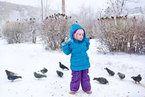 Cute little girl and pigeons