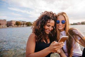 Female friends using smart phone