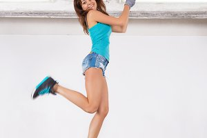 young beautiful woman jump and paints the wall with white paint
