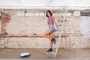 young beautiful woman paints white brick wall with paint brush a