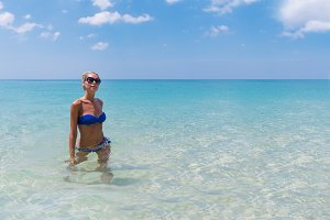 Young pretty slim blonde woman swimming in clear water on tropic