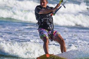 Athletic man jump on kite surf board sea waves
