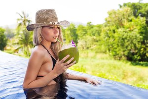 Young slim blonde woman hat drinks healthy detox coconut juice