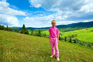 Small girl in summer mountains