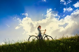 Girl with bike over sky
