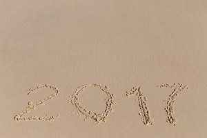 2017 sign on a beach sand