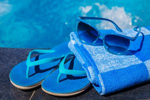 Blue slippers, sunglasses and towel on border of swimming pool