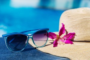 Sunglasses with flower and straw hat on border swimming pool