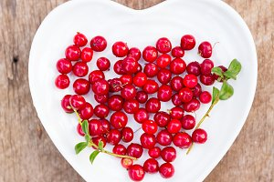 red forest cranberries in heart plate wooden background autumn