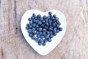 Fresh forest blueberries in heart plate on wooden background autumn