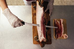 Butchery woman cutting ham.