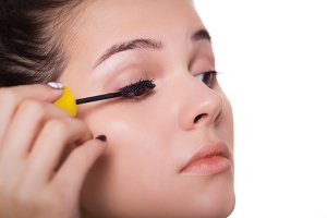 Young woman applying mascara - Makeup make-up