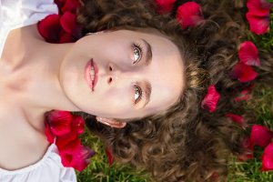Romantic woman in rose petals