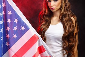 Girl holding US flag on flagpole