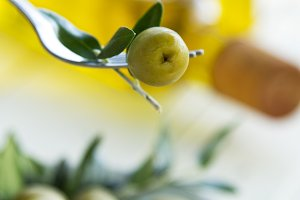 olive on fork with green background