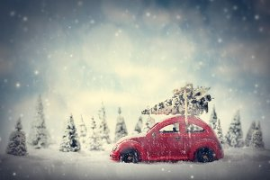 Retro toy car carrying tiny Christmas tree. Fairytale scenery with snow and forest.