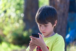 Child boy playing mobile phone