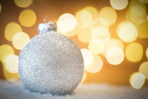 Christmas glass ball in snow. Glitter lights background