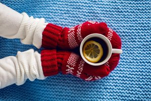 female hands in red mittens holding a mug of tea