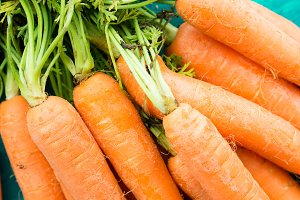 Bunch of carrots on green background. Top view