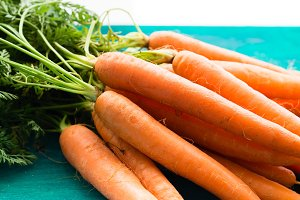 Bunch of carrots on green wooden background