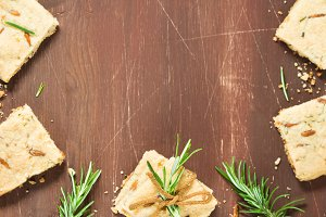 Dark wooden background with rosemary cookies
