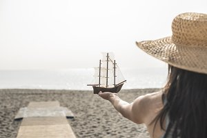 Woman with hat hold boat model