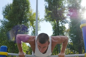 Athletic man doing push ups on bars at sports ground in city park. Strong young muscular guy training outdoor in summer. Athlete exercising at playground. Workout healthy lifestyle. Close up