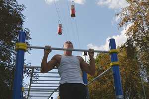 Strong muscular man doing pull ups in a park. Young athlete doing chin-ups and performs exercises on horizontal bars outdoor. Fitness muscular man training outside in summer. Workout sport lifestyle
