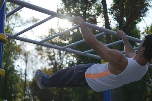 Athletic man doing lifting body on horizontal bar in city park. Male sportsman performs strength exercises during workout outdoor. Young guy demonstrates static exercise. Training outside