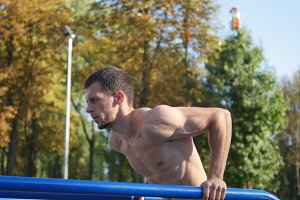 Athletic man doing push ups on parallel bars at sports ground in city park. Strong young muscular guy training outdoor in summer. Athlete exercising at playground. Workout healthy lifestyle. Closeup