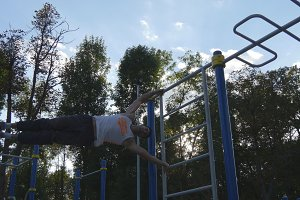 Young guy demonstrates human flag. Athletic man doing gymnastics elements on horizontal bar in city park. Male sportsman performs strength exercises during workout outdoor. Training outside
