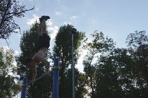 Strong muscular man doing a handstand in a park. Fit muscular male fitness guy doing stunts on horizontal bars outdoor. Athlete training performs a handstand at muscle outside. Workout sport lifestyle