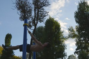 Athletic man doing gymnastics elements on horizontal bar in city park. Male sportsman performs strength exercises during workout outdoor. Young guy demonstrates static exercise. Training outside