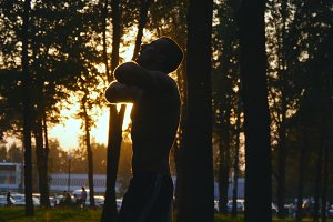 Silhouette of athlete jumping and warming up his hands before training in city park. Sun at background. Young strong muscular man stretches before workout at sunset. Sportsman doing exercise outdoor